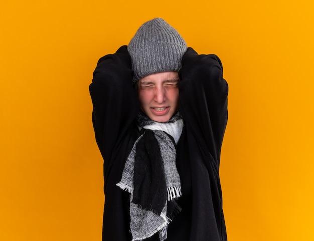 Ongezonde jonge vrouw met een warme muts en met sjaal om haar nek voelt zich ziek en heeft last van verkoudheid en griep die het hoofd aanraakt met sterke hoofdpijn die over de oranje muur staat