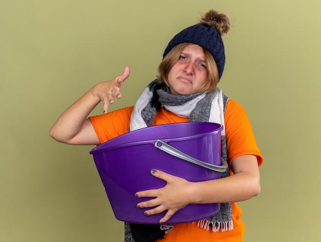 Ongezonde jonge vrouw met hoed met sjaal om haar nek voelt zich misselijk en heeft last van misselijkheid met een bekken dat over een groene muur staat