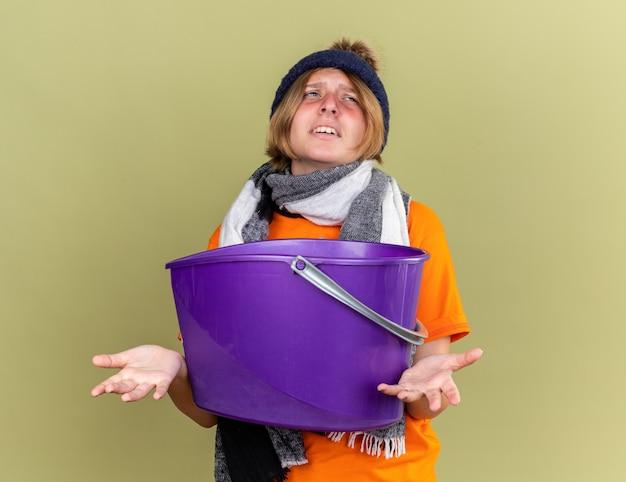Ongezonde jonge vrouw met hoed met sjaal om haar nek voelt zich misselijk en heeft last van misselijkheid terwijl ze een bekken vasthoudt en er verward uitziet terwijl ze over een groene muur staat