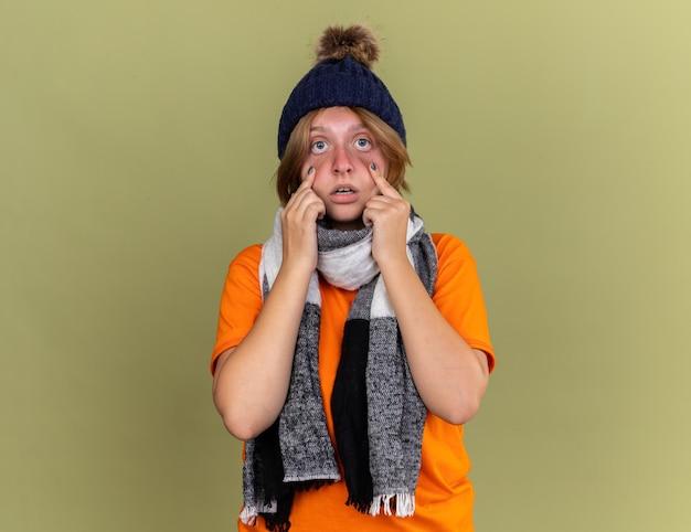 Ongezonde jonge vrouw met hoed met sjaal om haar nek voelt zich onwel en ziet er bang uit en lijdt aan een virus