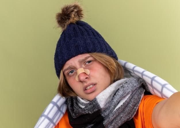 Ongezonde jonge vrouw met warme muts en sjaal om nek gewikkeld in deken die lijdt aan kou met patch op haar neus met droevige uitdrukking die over groene muur staat