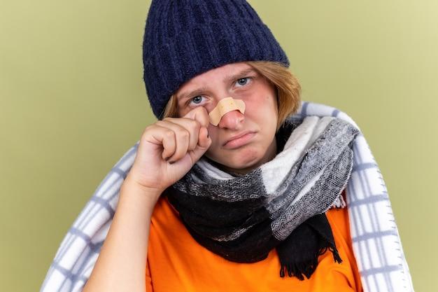 Ongezonde jonge vrouw met warme muts en sjaal om nek gewikkeld in een deken die zich onwel voelt en op neuspleister blijft plakken die verward kijkt met een droevige uitdrukking en bezorgd over groene muur staat
