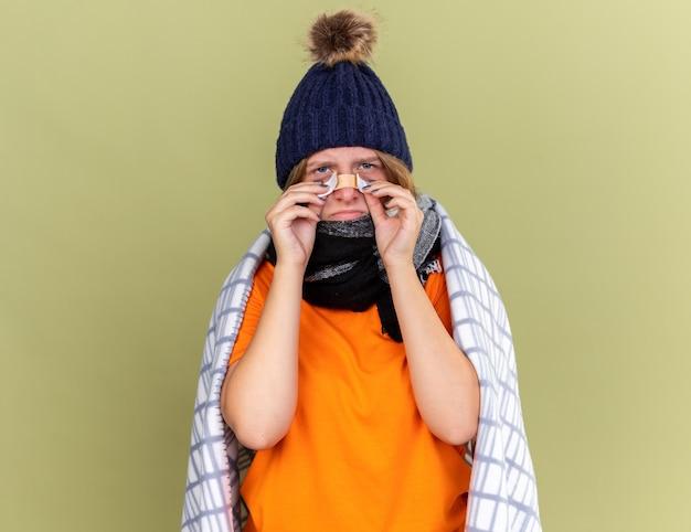 Ongezonde jonge vrouw met warme muts en sjaal om nek gewikkeld in een deken die zich onwel voelt met een pleister op de neus die er verward en bezorgd uitziet