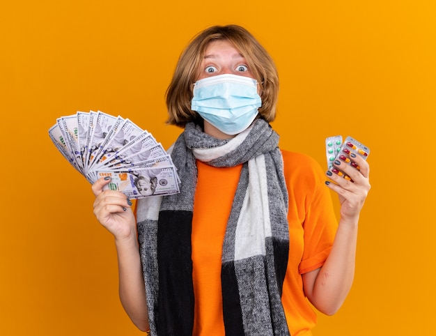 Ongezonde jonge vrouw met warme sjaal om haar nek met een beschermend gezichtsmasker met pillen en contant geld die verrast en verward over de oranje muur staat