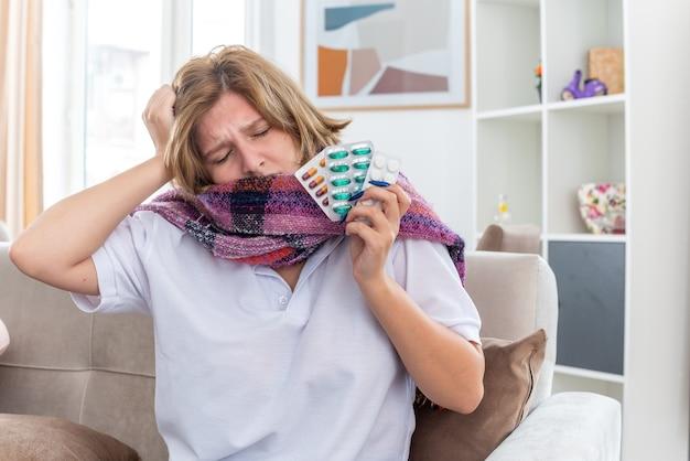 Ongezonde jonge vrouw met warme sjaal om nek die zich onwel en ziek voelt en lijdt aan griep en verkoudheid met verschillende pillen in haar handen en kijkt bezorgd zittend op de bank in een lichte woonkamer