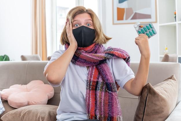 Ongezonde jonge vrouw met warme sjaal om nek met beschermend gezichtsmasker zich onwel en ziek voelen die lijden aan griep en verkoudheid houden pillen op zoek verward zittend op de bank in lichte woonkamer