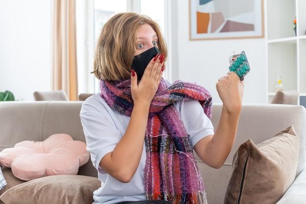 Ongezonde jonge vrouw met warme sjaal om nek met gezichtsbeschermend masker voelt zich onwel en ziek en lijdt aan griep en verkoudheid die pillen vasthoudt en er verward uitziet zittend op de bank in een lichte woonkamer