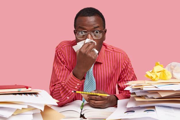 Ongezonde mannelijke volwassene gebruikt zakdoek, heeft verkoudheid, loopneus, werkt freelancer thuis, draagt spiraalvormig notitieboekje