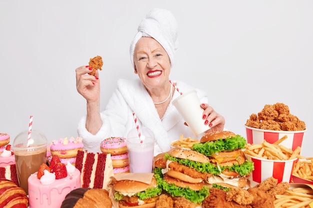 Ongezonde overeten levensstijl. blije oude dame lacht positief drinkt frisdrank eet fastfood