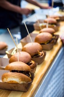 Ongezonde straatvoedselburgers met vlees en kaas op een openluchtfestivallocatie