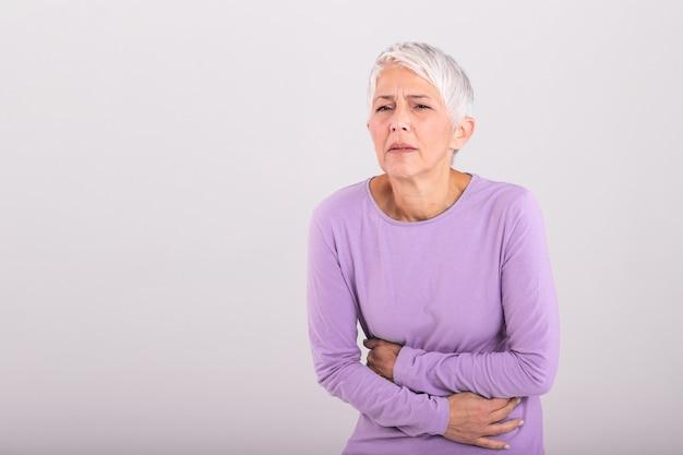 Ongezonde volwassen vrouw met buik, ongemak, gezondheidsprobleem concept, ongelukkig oudere vrouwelijke zittend op bed, buikpijn lijden