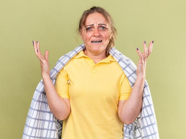 Ongezonde vrouw gewikkeld in deken die zich onwel voelt, griep en verkoudheid heeft en koorts heeft en er gefrustreerd uitziet terwijl ze haar armen opsteekt