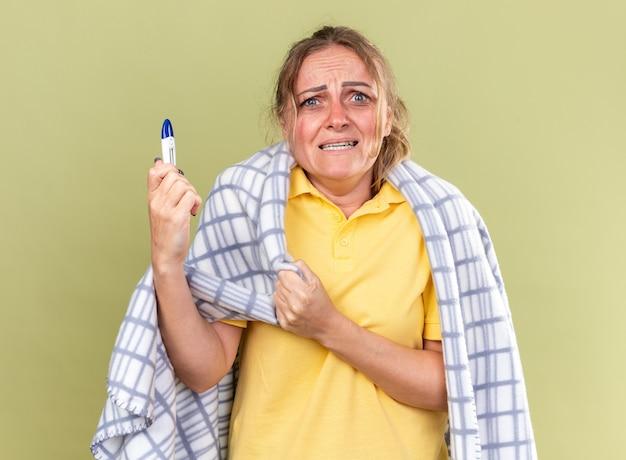 Ongezonde vrouw gewikkeld in een deken die zich onwel voelt en lijdt aan griep en verkoudheid met koorts die een thermometer vasthoudt en er bezorgd uitziet