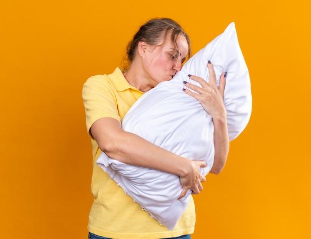 Ongezonde vrouw in geel shirt die lijdt aan griep en verkoudheid knuffelkussen voelt zich beter kussen kussen dat over oranje muur staat