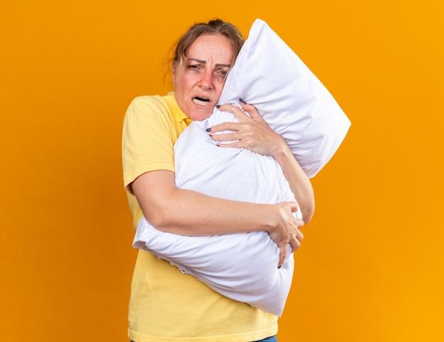 Ongezonde vrouw in geel shirt die zich onwel voelt en lijdt aan griep en koud knuffelkussen dat over oranje muur staat