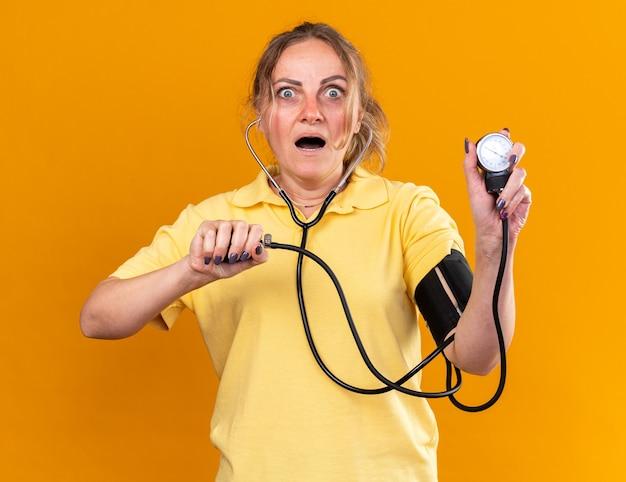 Ongezonde vrouw in geel shirt die zich onwel voelt en lijdt aan griep en verkoudheid die haar bloeddruk meet met behulp van tonometer die bezorgd over de oranje muur staat