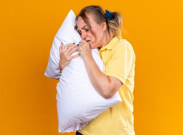 Ongezonde vrouw in geel shirt die zich onwel voelt en lijdt aan griep en verkoudheid knuffelt kussen hoestend over oranje muur