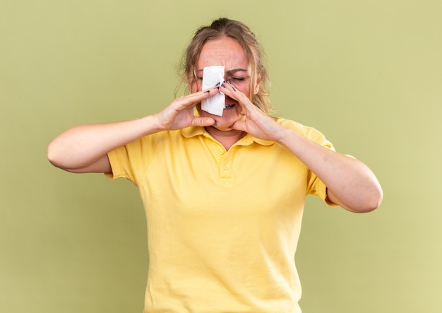 Ongezonde vrouw in geel shirt die zich vreselijk voelt en lijdt aan een loopneus met sterke hoofdpijn die over een groene muur staat