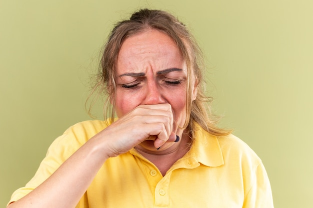 Ongezonde vrouw in geel shirt die zich vreselijk voelt, lijdt aan griep en verkoudheid die een loopneus afveegt en niest over een groene muur