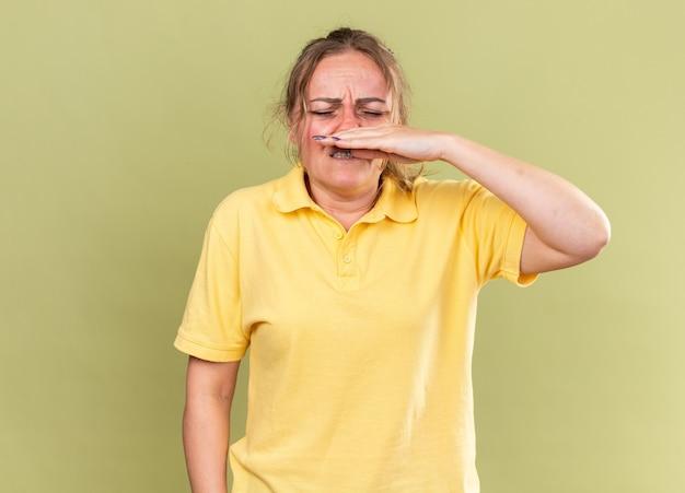 Ongezonde vrouw in geel shirt die zich vreselijk voelt, lijdt aan griep en verkoudheid die een loopneus afveegt