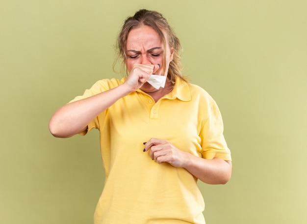 Ongezonde vrouw in geel shirt die zich vreselijk voelt, lijdt aan griep en verkoudheid met koorts die hoest over groene muur staat