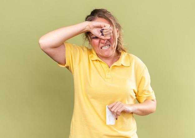 Ongezonde vrouw in geel shirt voelt zich vreselijk als ze haar voorhoofd aanraakt en lijdt aan sterke hoofdpijn vanwege een verstopte neus met griep die over de groene muur staat