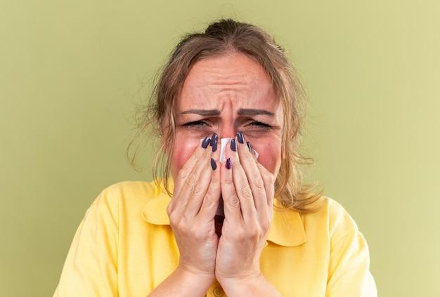 Ongezonde vrouw in geel shirt voelt zich vreselijk, lijdt aan griep en verkoudheid, lopende neus die niest in weefsel