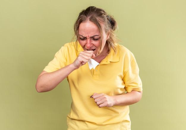 Ongezonde vrouw in geel shirt voelt zich vreselijk, lijdt aan griep en verkoudheid met koorts hoesten