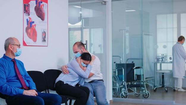 Ongunstig nieuws van arts aan jong stel in de wachtruimte van het ziekenhuis tijdens de uitbraak van het coronavirus. man en vrouw dragen gezichtsmasker tegen infectie met covid 19.
