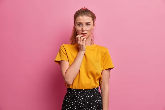 Onhandig europees meisje kijkt zenuwachtig, maakt zich zorgen over gestolen geld, ziet er intens uit, heeft vreselijke gedachten in gedachten, is in paniek