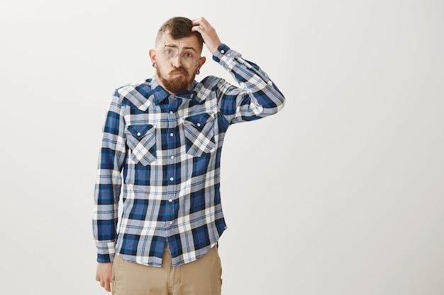 Onhandige, bebaarde jongeman met een scheve bril die besluiteloos en verbaasd kijkt, krabbelt op zijn hoofd
