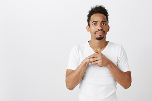 Onhandige en verwarde afro-amerikaanse man die er ingewikkeld uitziet