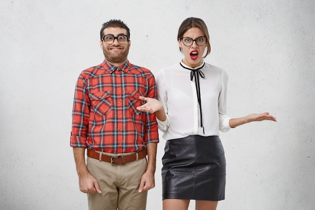 Onhandige grappige ongeschoren mannelijke geek staat naast mooie vrouw met rode lippen