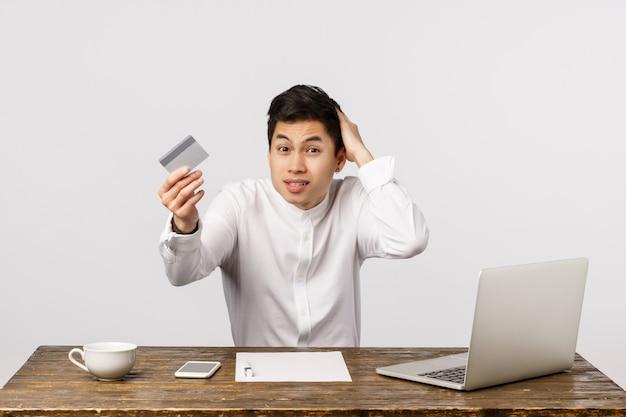 Onhandige knappe chinese kerel die bureau met laptop, documenten en thee zit, creditcard toont, het hoofd van de krabben ongerust gemaakt, zich verontschuldigend heb geen geld betalen