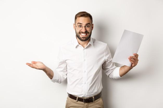 Onhandige manager toont document en haalt zijn schouders op, ziet er schuldig uit, staat op