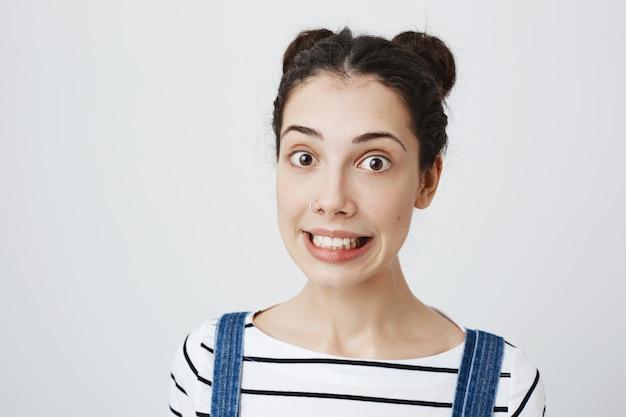 Onhandige schattige vrouw klemt haar tanden op elkaar en glimlacht ongemakkelijk