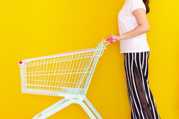 Onherkenbaar aziatisch meisje dat op een winkelwagentje of karretje springt, schiet op een felgele achtergrond in de studio. vrouw houden en duwen op een vintage winkelwagentje close-up. vrouw winkelen concept.