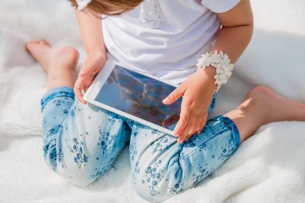 Onherkenbaar babymeisje met tablet, gekleed in witte polo en spijkerbroek, op blote voeten zittend op de witte dekking in het park.