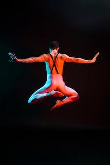 Onherkenbaar balletdanser springen met gespreide armen in de schijnwerpers