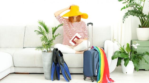 Onherkenbaar boos meisje met gele hoed blijft thuis en plant een reis op vakantie. wachten op reizen.