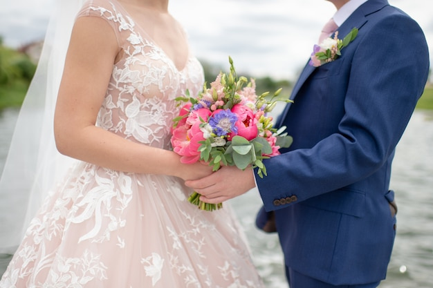 Onherkenbaar bruidspaar met bloemen in hun handsc poseren voor fotograaf in de natuur
