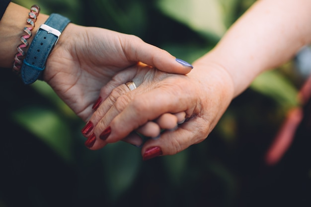 Onherkenbaar grootmoeder en haar kleindochter hand in hand met liefde