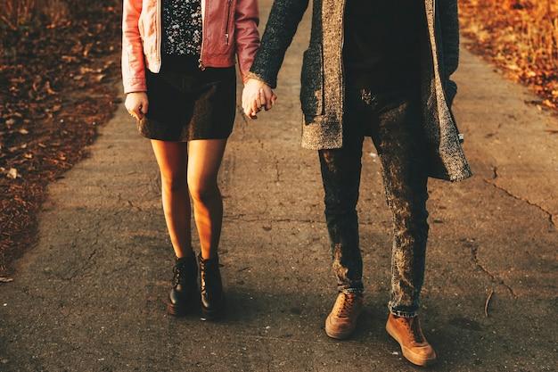 Onherkenbaar jonge man en vrouw hand in hand en wandelen langs de asfaltweg van het platteland op herfstdag. gewas paar lopen op platteland weg