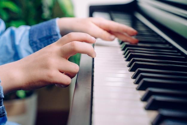 Onherkenbaar kind piano spelen. detail van weinig jongenshanden wat betreft een toetsenbord thuis. student van pianist musicus die klassieke muziek repeteert. educatieve muzieklevensstijl.