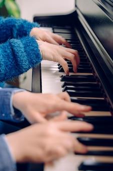 Onherkenbaar kind piano spelen met muziekleraar. het detail van weinig jongen overhandigt thuis wat betreft toetsenbord. student van pianist musicus die klassieke muziek repeteert. educatieve muzikale levensstijl.
