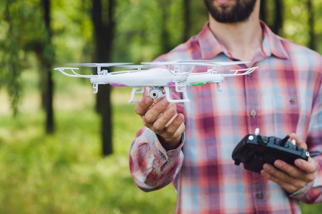 Onherkenbaar man met drone met camera in bos.