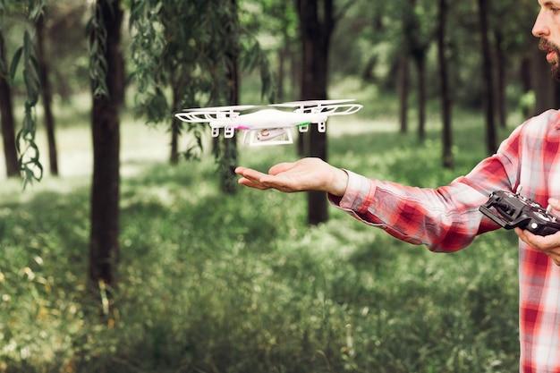 Onherkenbaar man met quadrocopter in bos.