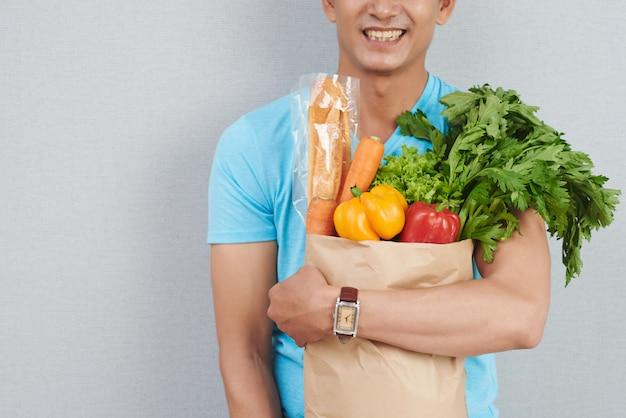 Onherkenbaar man poseren met papieren zak vol met verse groenten, groene kruiden en stokbrood