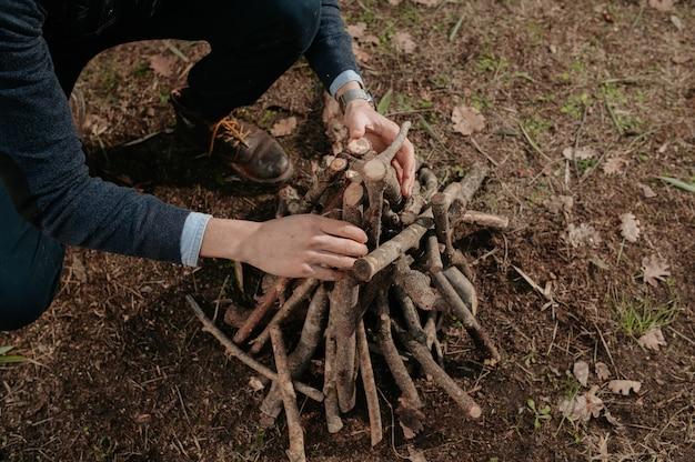 Onherkenbaar man stapel hout voorbereiden om in brand te steken. camping, natuurlijke levensstijl concept.