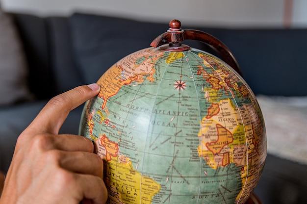 Onherkenbaar mannelijk toeristen land op retro wereldbol plukken tijdens het plannen van reizen